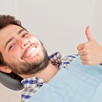 Młody szczęśliwy mężczyzna i kobieta w badaniu stomatologicznym u dentysty