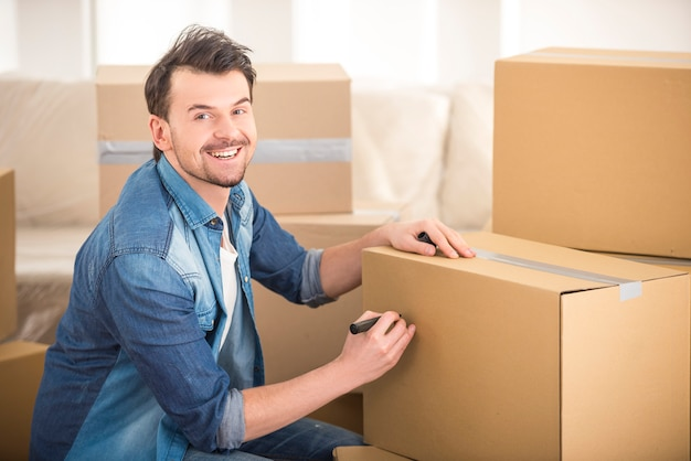 Młody szczęśliwy mężczyzna podpisywania pudełko w nowym domu.