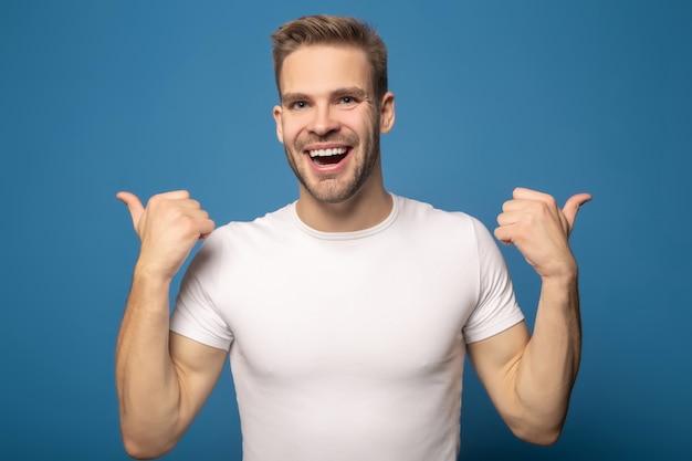Młody szczęśliwy mężczyzna pokazuje aprobaty odizolowywać na błękicie