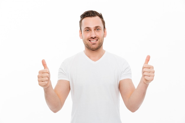 Młody szczęśliwy mężczyzna pokazuje aprobaty.
