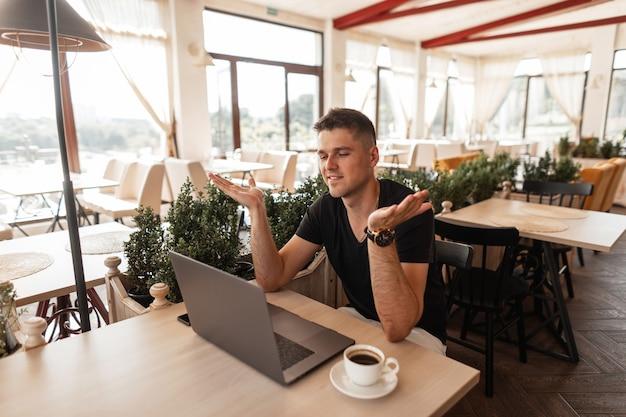Młody szczęśliwy mężczyzna siedzi w kawiarni vintage z nowoczesnym laptopem i cieszy się z sukcesu w tworzeniu nowego projektu. atrakcyjny pozytywny freelancer pracuje zdalnie. czas pracy.