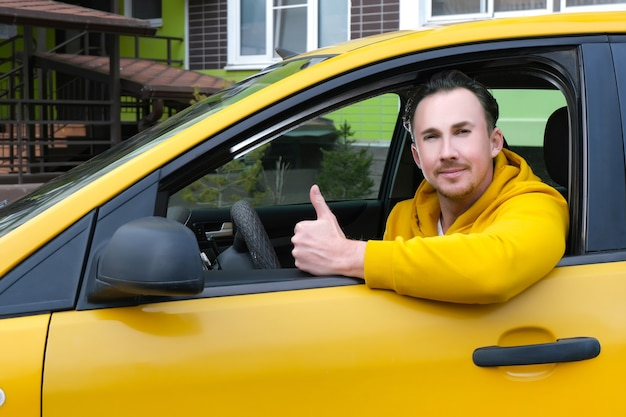 Młody szczęśliwy mężczyzna taksówkarz siedzi za kierownicą taksówki i pokazuje jak