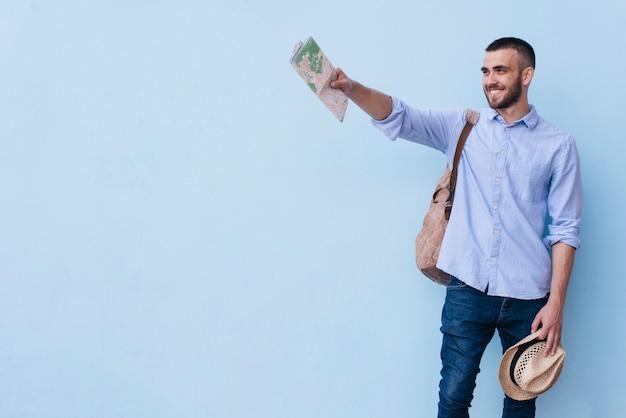 Młody szczęśliwy mężczyzna trzyma mapę i kapelusz pokazując coś stojącego na niebieskim tle