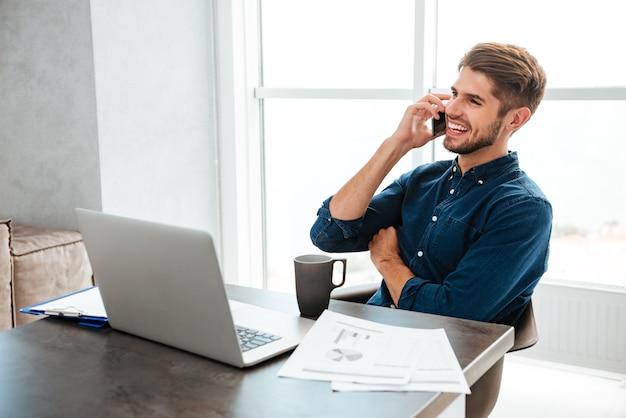 Młody szczęśliwy mężczyzna ubrany w niebieską koszulę, pije herbatę i siedzi obok stołu z laptopem i dokumentami, rozmawiając przy swoim telefonie