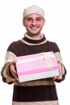 Młody szczęśliwy mężczyzna uśmiecha się dając pudełko