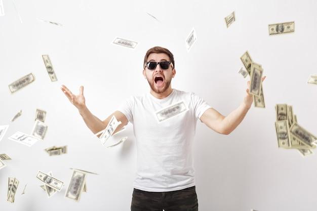 Młody szczęśliwy mężczyzna z brodą w białej koszuli stojący pod pieniędzmi
