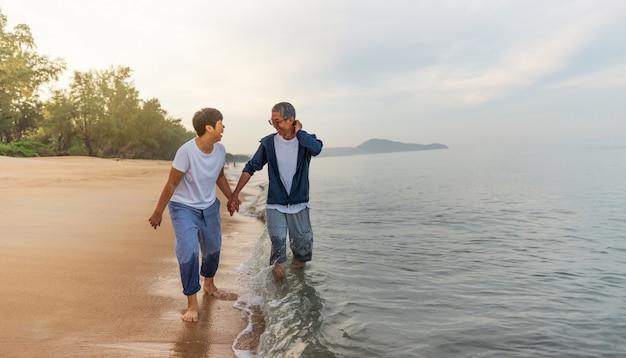 Młody szczęśliwy międzyrasowy para spaceru na plaży uśmiechający się gospodarstwa wokół siebie.