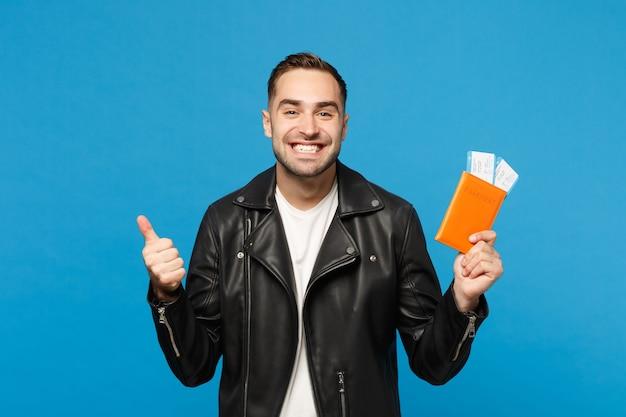 Młody szczęśliwy nieogolony mężczyzna w czarnej kurtce biały t-shirt trzymać w ręku bilety paszportowe na białym tle na tle niebieskiej ściany. pasażer wyjeżdżający za granicę. koncepcja podróży lotniczej makieta miejsca kopiowania