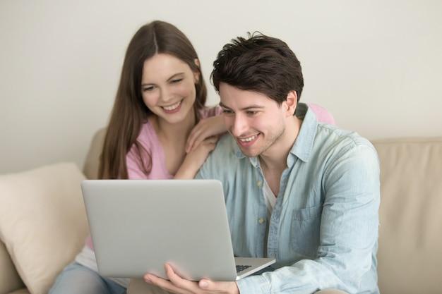 Młody szczęśliwy pary obsiadanie używać laptop