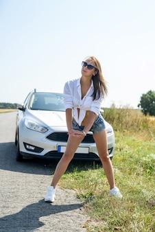 Młody szczęśliwy piękny model w pobliżu jej samochodu na letnią wycieczkę