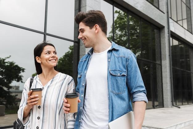 Młody szczęśliwy podekscytowany niesamowity kochający para studentów na zewnątrz na zewnątrz przy ulicy spaceru pijąc kawę rozmawiając ze sobą.