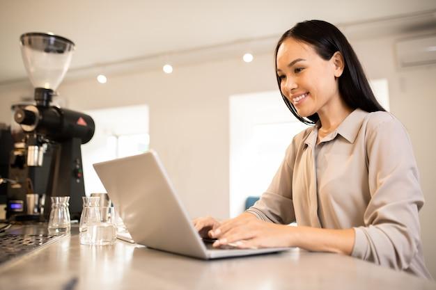 Młody szczęśliwy przedsiębiorca żeński siedzi w miejscu pracy przed laptopem podczas surfowania w sieci dla kreatywnych pomysłów