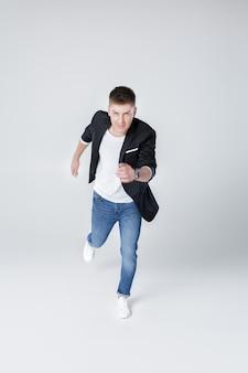 Młody szczęśliwy przystojny mężczyzna w cajgach i kurtce skoki