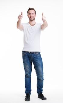 Młody szczęśliwy przystojny mężczyzna z kciukami do góry podpisuje przypadkowe w pełnym wzroście - na białym tle