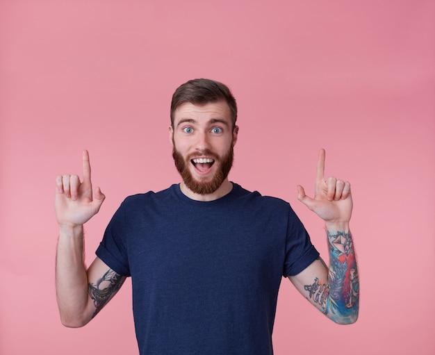 Młody szczęśliwy rudobrody młody chłopak, z szeroko otwartymi ustami ze zdziwienia, chce zwrócić twoją uwagę wskazując palcami w górę, aby skopiować przestrzeń odizolowaną na różowym tle.