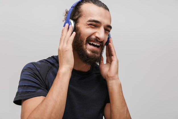Młody szczęśliwy sportowiec ubrany w dres, uśmiechający się podczas słuchania muzyki ze słuchawkami izolowanymi na białej ścianie