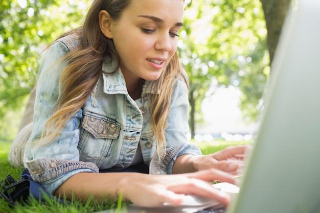 Młody szczęśliwy studencki lying on the beach na trawie używać laptop