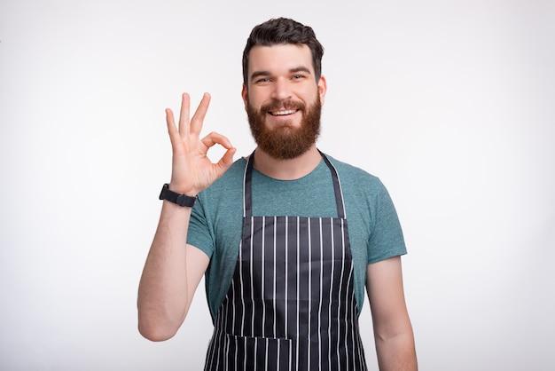 Młody szczęśliwy szef kuchni pokazuje ok gest nad białym tłem