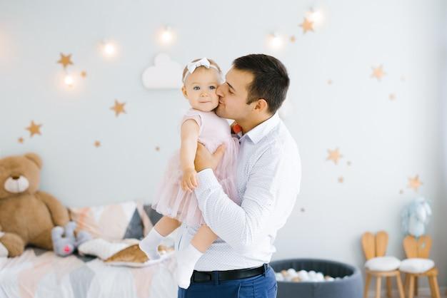 Młody szczęśliwy tata trzyma w ramionach uśmiechniętą córkę i całuje ją w policzek w dziecięcym pokoju