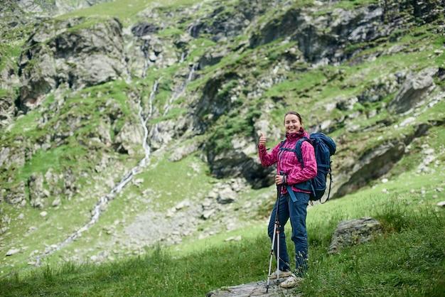 Młody szczęśliwy turysta famele z kijami trekkingowymi i plecakiem stoi na kamieniu u podnóża gór. dziewczyna ono uśmiecha się kamera i pokazuje aprobaty