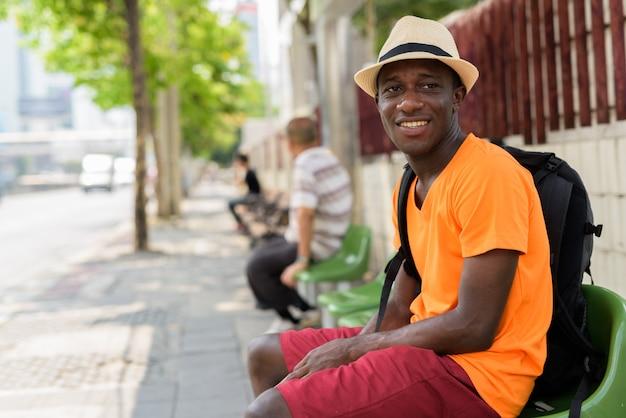 Młody szczęśliwy turysta mężczyzna uśmiecha się i myśli siedząc na przystanku autobusowym na ulicach bangkoku w tajlandii
