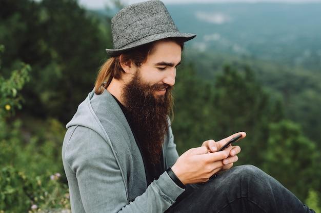Młody szczęśliwy turysta siedzi na szczycie góry i trzyma nowy telefon.