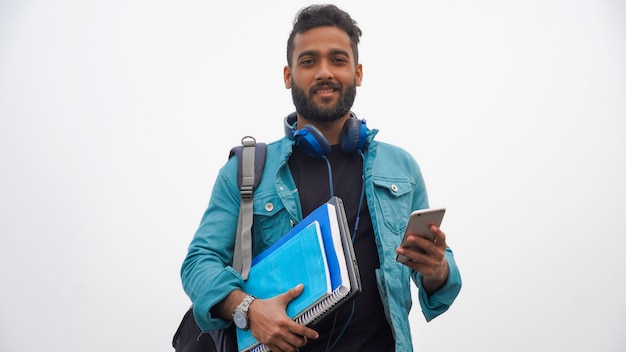 Młody szczęśliwy uczeń z książkami i laptopem za pomocą wiszącej ozdoby