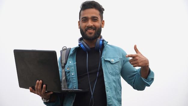 Młody szczęśliwy uczeń z laptopem i hełmofonem