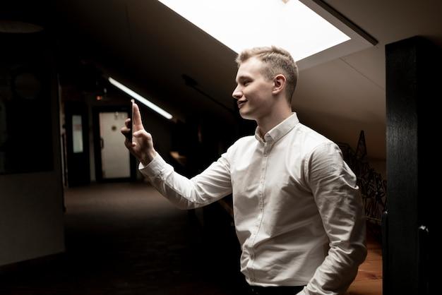 Młody szczęśliwy urzędnik robi selfie w miejscu pracy z smartphone