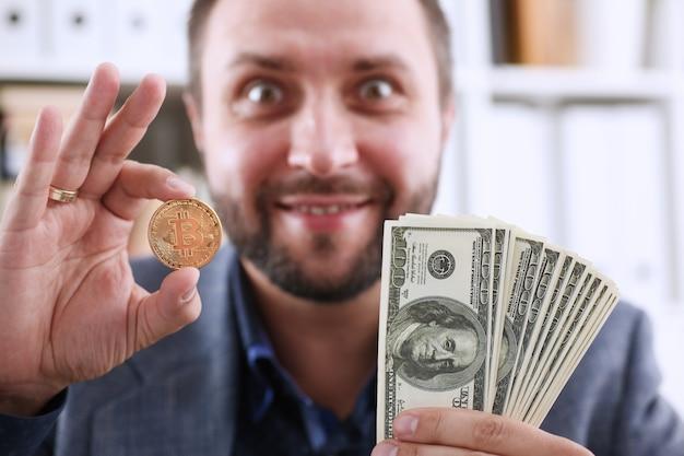 Młody szczęśliwy uśmiechnięty biznesmen trzyma w ręku dolara i monetę bitcoinów zamiast okularów, raduje się, że miała czas kupić, aby wyprodukować moment deshego przed wzrostem ceny i wzrostem.