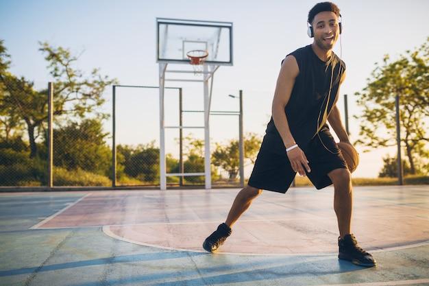 Młody szczęśliwy uśmiechnięty murzyn uprawia sport, gra w koszykówkę o wschodzie słońca, słuchanie muzyki na słuchawkach, aktywny tryb życia, letni poranek