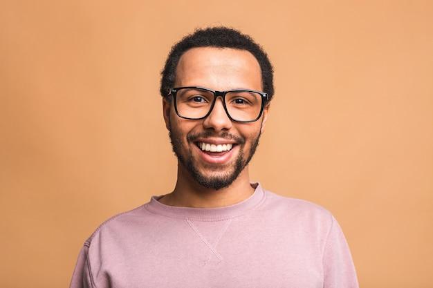 Młody szczęśliwy uśmiechnięty zabawny mężczyzna na białym tle na beż.