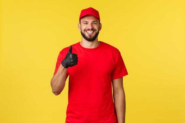 Młody szczęśliwy, zadowolony brodaty kurier w czapce i koszulce firmy, noszący rękawice ochronne, pokazujący kciuk do góry i uśmiechnięty