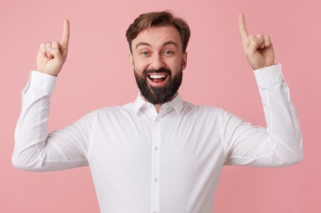Młody szczęśliwy, zdumiony przystojny brodaty mężczyzna, ubrany w białą koszulę, zwraca uwagę palcami wskazującymi na górze przestrzeni kopii. patrząc w kamerę i uśmiechając się na białym tle na różowym tle.