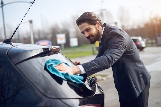 Młody szczęśliwy zmotywowany pracowity młody biznesmen w garniturze do czyszczenia tylnej szyby swojego samochodu ściereczką z mikrofibry na stacji samoobsługowej mycia samochodów.