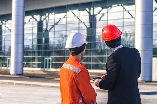 Młody szef i pracownik omawiają projekt budowlany na tablecie