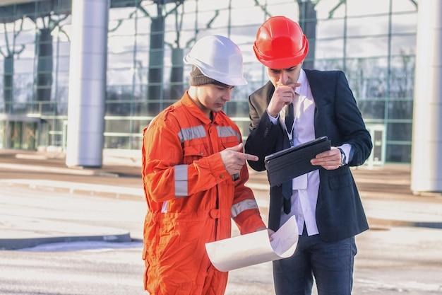 Młody szef i pracownik w rozmowie omawiającej projekt budowlany