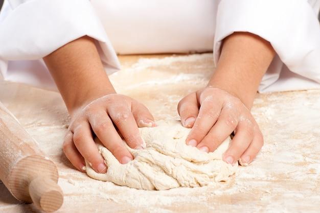 Młody szef kuchni pracuje ciasto z rękami