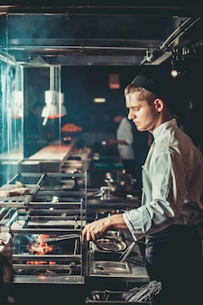 Młody szef kuchni w białym mundurze do gotowania mięsa
