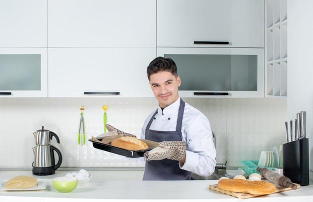 Młody szef kuchni w mundurze noszącym uchwyt