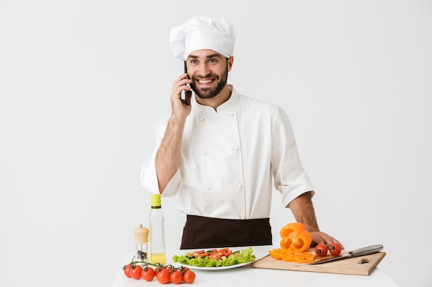 Młody szef kuchni w mundurze uśmiecha się i rozmawia na smartfonie podczas gotowania sałatki warzywnej izolowanej nad białą ścianą