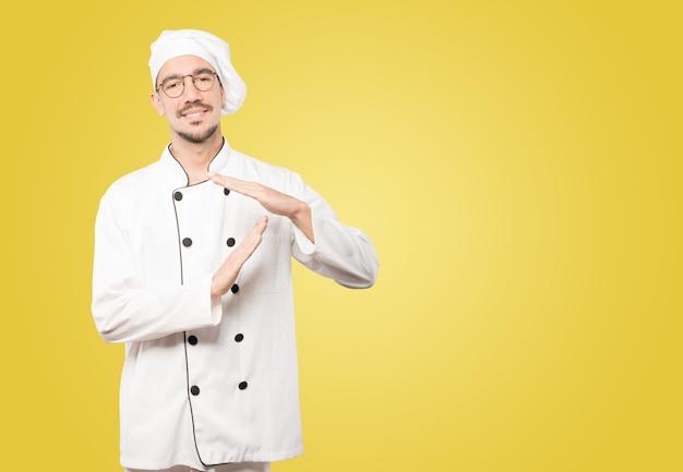 Młody szef kuchni, wykonując gest rękoma