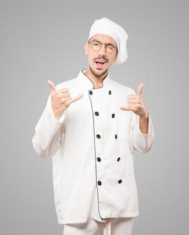 Młody szef kuchni wykonując gest zawołania ręką