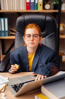 Młody szef. ładna poważna dziewczyna patrząca na ciebie w dużym garniturze