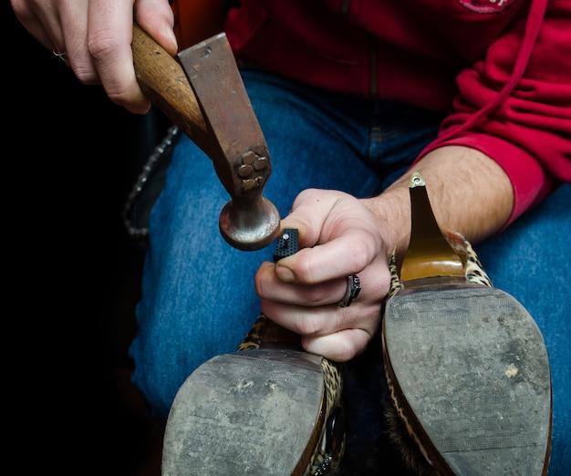 Młody szewc naprawy starej pary butów pięty z narzędziem hamer