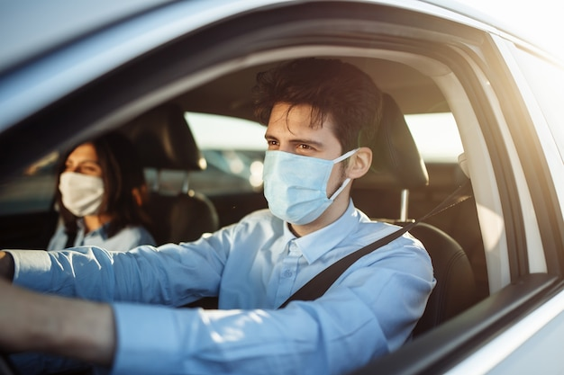 Młody taksówkarz chłopiec daje pasażerowi przejażdżkę w sterylnej masce medycznej.