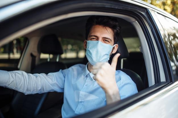 Młody taksówkarz pokazuje kciuk w górę siedząc w samochodzie i nosząc ochronną sterylną maskę medyczną, ciężko pracuje podczas epidemii koronawirusa.