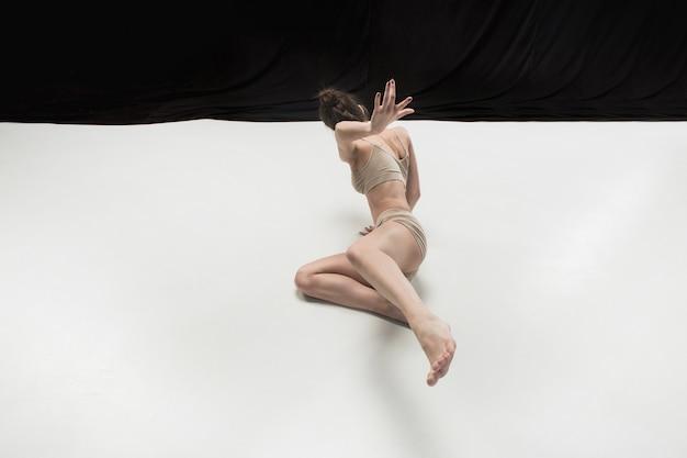 Młody tancerz nastolatek na białej powierzchni podłogi.