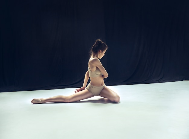 Młody tancerz nastolatek taniec na białym piętrze studio.