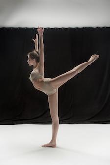 Młody tancerz nastolatek taniec na tle studio białym piętrze. projekt ballerina.